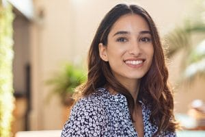 Closeup face of happy smiling young woman. Portrait of beautiful latin girl looking at camera. Confident casual girl sitting at cafeteria.