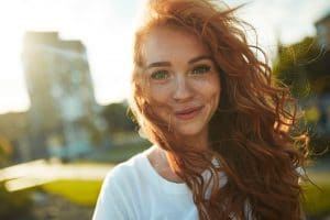 Portraits of a charming red-haired girl with a cute face. Girl posing for the camera in the city center. She has a wonderful mood and a lovely smile.