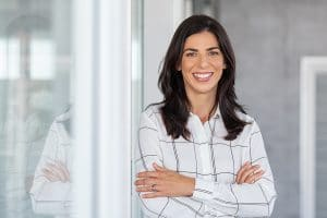 Portrait of middle aged businesswoman in modern office looking at camera. Confident business woman with arms crossed standing while leaning against glass wall. Proud brunette woman smiling in formalwear with copy space.